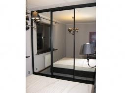 Szafa w sypialni. Wnętrze szafy (boki, wieńce, półki, cokoły) oraz profile aluminiowe drzwi przesuwanych są czarne. W tej samej kolorystyce co pozostałe elementy wyposażenia pokoju. Jako wypełnienie drzwi przesuwanych Klienci wybrali lustro co optycznie powiększyło pomieszczenie.