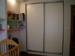 Szafa wnękowa z drzwiami przesuwanymi w systemie RAUMPLUS z wypełnieniem lakierowanym z poprzecznym podziałem wyfrezowanym w płycie MDF. Idealne dopełnienie wyposażenia pokoju dziecinnego.