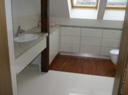 Łazienka na poddaszu. Zgrabne połączenie kamienia, szafek z frontami z MDF-u lakierowanymi na wysoki połysk oraz drewnianych elementów wnętrza. Pod oknami specjalnie wykonane na wymiar szafki szufladowe - dopasowane do skosu.