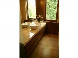 Szafka łazienkowa podwieszana. Wykonana z forniru w systemie bezuchwytowym. Fornir w postaci paneli jest zamontowany na ścianie w które są dopasowane do kamienia.
