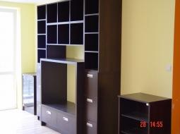 Regał pokojowy z półkami na książki oraz miejscem na duży telewizor wyznaczonym poprzez obramowanie wykonane z płyty podwójnej grubości. Duża ilość głębokich szuflad podnosi funkcjonalność mebli. Kolorystyka - orzech ciemny.