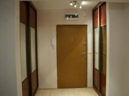 Szafy wnękowe w przedpokoju w systemie RAUMPLUS z drzwiami przesuwanymi. Wypełnieni drzwi w szafie: płyta meblowa i lustro.