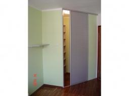 Drzwi przesuwane - przejście do garderoby. Wyposażenie garderoby wykonano z płyt meblowych, kolor klon.