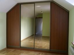 Szafa wnękowa na poddaszu wykonana w systemie RAUMPLUS (drzwi przesuwne). Wypełnienie drzwi z płyty meblowej oraz luster. Tego rodzaju zabudowa dzięki różnorodnym formom adaptacji wnętrza pozwala na optymalne wykorzystanie miejsca na poddaszu.